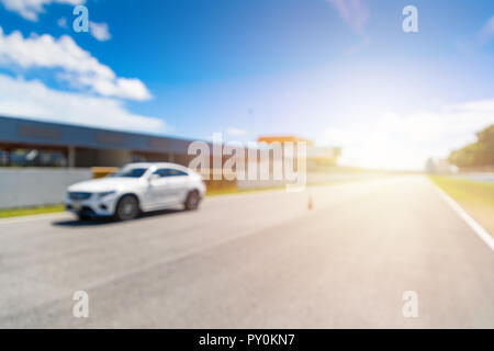 Abstract blur and bokeh. White Luxury car in racetrack and speed racing back ground clear sky. Sunlight and flare concept. - Stock Photo