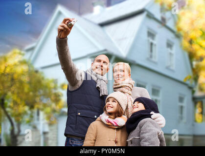 family takes autumn selfie by camera over house - Stock Photo
