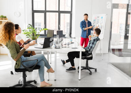 man showing smartphone user interface at office - Stock Photo