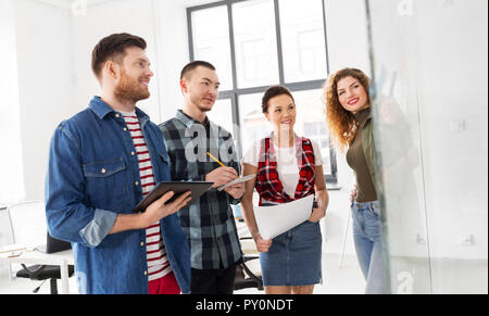 creative team looking at glass board at office - Stock Photo