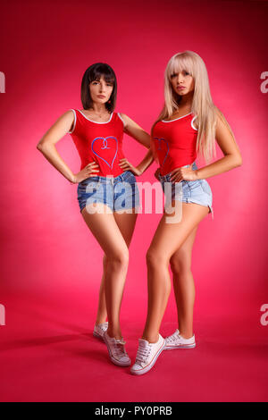 two beautiful athletic young women posing in Studio on pink background. - Stock Photo