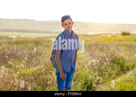 happy young man standing with backpack outdoors on Sunny day. - Stock Photo