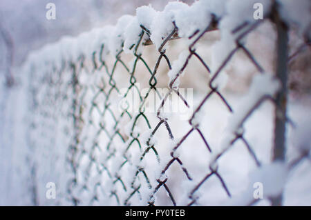 Closeup of a mesh fence covered in a thick layer of white fresh fluffy snow against a blurred purple background. Cold winter day in January