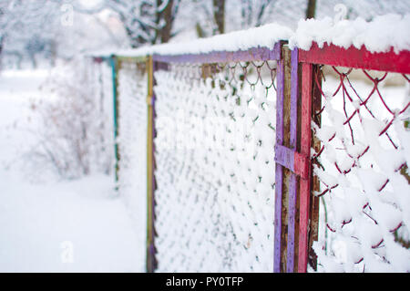 Closeup of a colorful mesh fence covered in a thick layer of white fresh fluffy snow against blurred trees and bushes on the background. Cold winter d