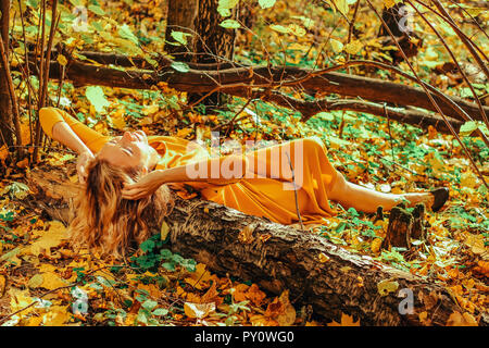 Young beautiful girl in a long yellow dress lying on the ground of the autumn park with fallen yellow leaves - Stock Photo