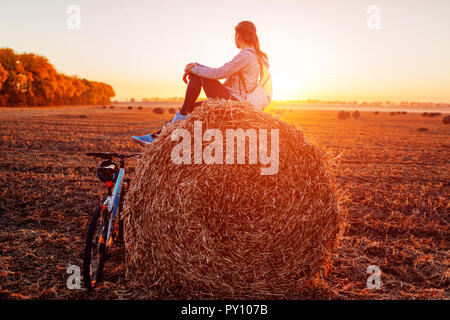 Young bicyclist sitting on haystack after a ride. Woman having rest in autumn field admiring view. Sportive lifestyle - Stock Photo