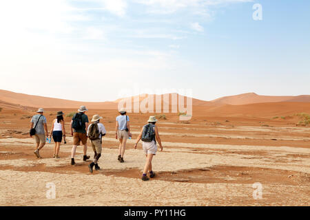 Namibia tourists -a group of tourists on a guided tour with their tour guide, in the Namib Desert at Sossusvlei, Namibia Africa - Stock Photo
