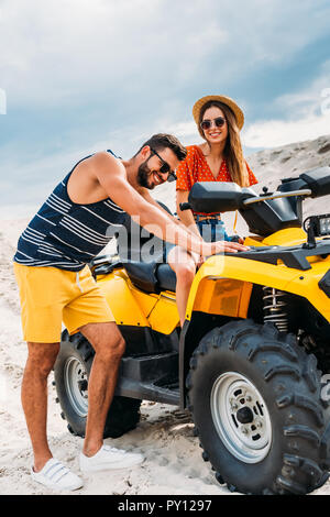 handsome young man pushing atv with his girlfriend got stuck in desert - Stock Photo