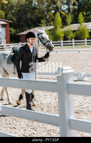 smiling handsome male equestrian walking near horse at horse club - Stock Photo