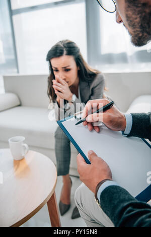 cropped image of psychologist taking notes and sad patient looking down in doctors office - Stock Photo