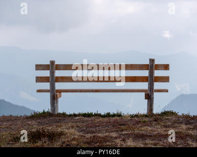 Close up image with focus of bench with mountains in the background - Stock Photo