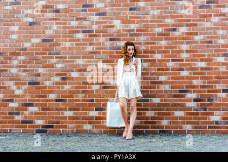 shocked young woman with shopping bags using smartphone in front of brick wall - Stock Photo