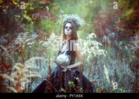 Young woman with Halloween make-up in fairytale forest with pumpkin. - Stock Photo