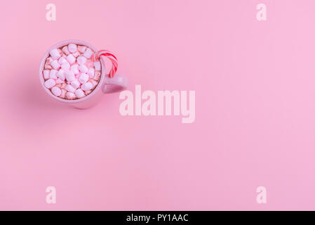 Christmas context in a minimal style with a pink cup of hot chocolate, mini marshmallows and an Xmas candy cane, on a pink paper background. - Stock Photo