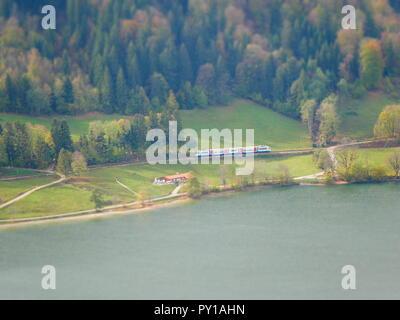 Tilt shift image of train in autumn landscape next to lake - Stock Photo