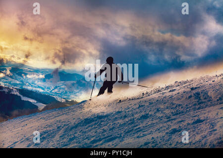 Skier going downhill at sunset - Stock Photo
