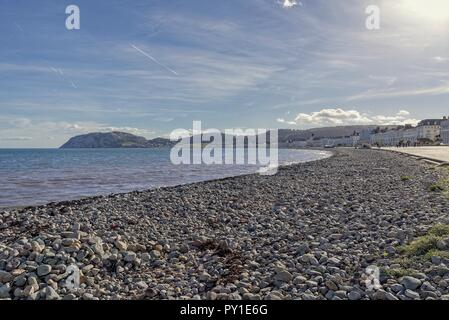 A view of Llandudno's curving shoreline lined by white fronted hotels. The Little Orme headland is in the distance and a blue sky is above. - Stock Photo