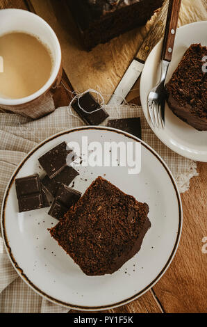 Chocolate pound cake pieces on white plates. Brown toned, wooden background, directly above. - Stock Photo