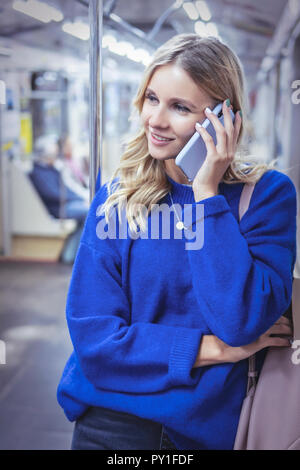 woman talking on phone in the subway - Stock Photo