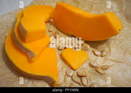 Slices of organic and fresh natural pumpkins, with seeds around and decoration in shape of heart. Healthy food concept - Stock Photo