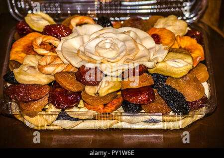 Dried fruits from apples, prunes,apricots,peaches,pears and melons in a plastic box - Stock Photo