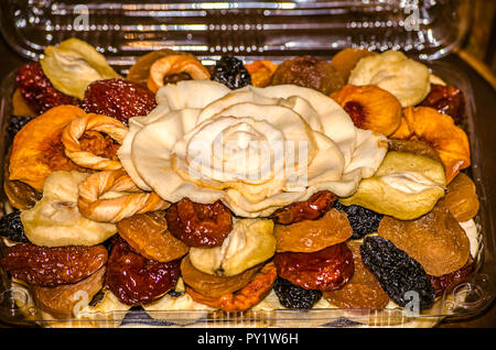 Candied of fruits and dried fruits from apples, prunes, apricots, peaches, pears and melon in a plastic box - Stock Photo