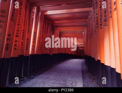 Senbon torii passage of vermillion Torii gates leading to the outer Shinto shrine of Fushimi Inari Taisha, Kyoto, Japan. - Stock Photo