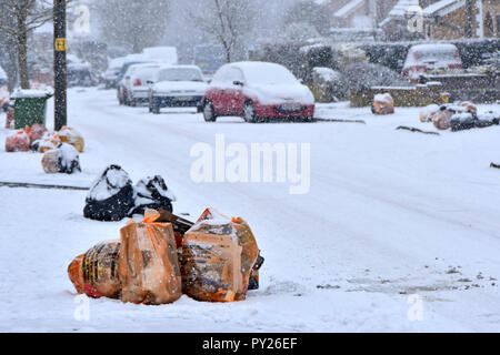 Winter street scene bags of recycle waste & black sack landfill rubbish snow covered on pavement for council waste management team collection truck UK - Stock Photo