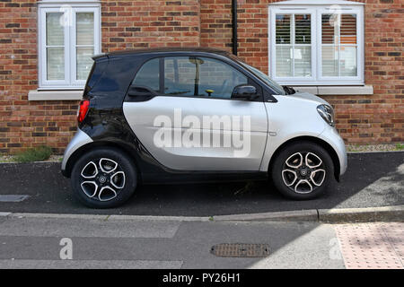 A Daimler Smart small cars compact size fits onto narrow private tarmac pavement car parking spot & space outside apartment window Essex England UK - Stock Photo