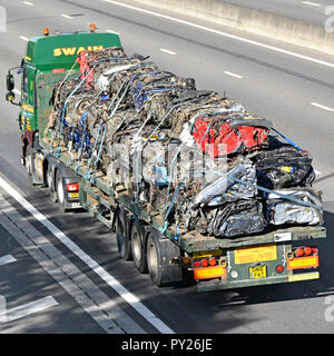 HGV lorry transport truck & articulated flat bed trailer driving along motorway heavy load of crushed cube scrap metal cars for recycling England UK - Stock Photo
