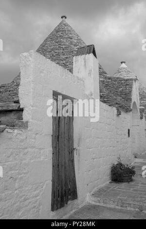 White-washed conical roofed trulli house behind white washed wall in the town of Alberobello in Puglia, Southern Italy. Photographed in monochrome. - Stock Photo