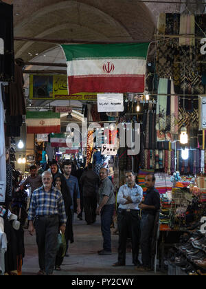 ISFAHAN, IRAN - AUGUST 8, 2018: Street of the Isfahan bazar with an Iranian flag hanging, in a covered alley of the market. Symbol of the Persian arch - Stock Photo