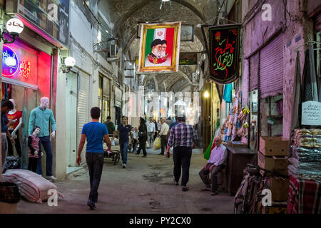 ISFAHAN, IRAN - AUGUST 20, 2018: Street of the Isfahan bazar with an Iranian flag hanging with the portraits of the 2 Supreme leaders of the Islamic R - Stock Photo