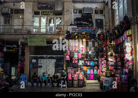 ISFAHAN, IRAN - AUGUST 20, 2018: Street of the Isfahan bazar in the afternoon, with merchants sitting and selling school backpacks in the covered mark - Stock Photo