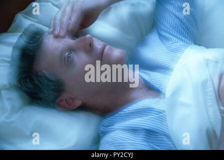 Man with a headache is tossing and Turning at night in bed, USA - Stock Photo