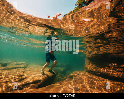 Underwater view of a boy walking in a lake, Lake Superior, United States - Stock Photo