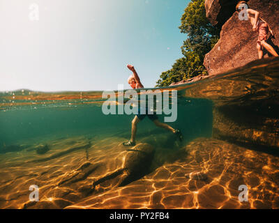 Boy running in a lake, Lake Superior, United States - Stock Photo