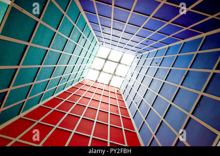 Abstract perspective of vertical lobby ceiling with skylight and strong geometry and symmetry and dramatic colors as background with space for copy - Stock Photo