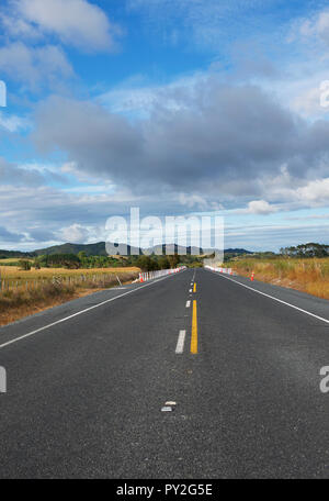 Empty straight road leading to the mountains, New Zealand - Stock Photo