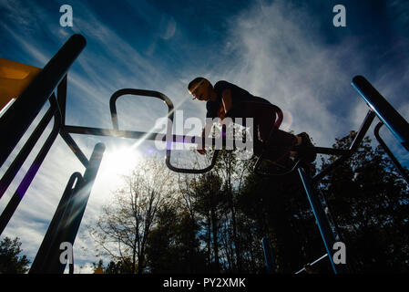 A 12-year old boy climbs across the monkey bars at a playground on a sunny day. - Stock Photo