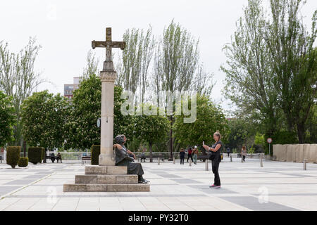 León, Spain: Pilgrims on the Camino Frances route of the Way of St. James take photos with the bronze sculpture of a pilgrim in Plaza San Marcos. - Stock Photo