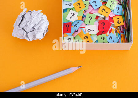 Pencil with crumpled paper ball and question marks in a paper box on yellow background. Concept image. Close up. - Stock Photo