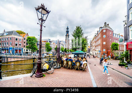 Typical scene of a gathering of tourists and locals at a cafe at the Prinsengracht canal in the Jordaan in the old city center of Amsterdam, Holland - Stock Photo