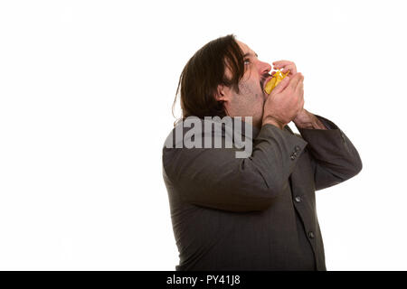 Fat Caucasian businessman eating mouthful of chips - Stock Photo