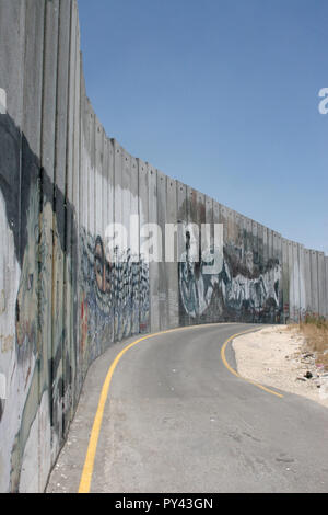 JERUZALEM, ISRAEL - JULI 11, 2004: Empty street along the tall Israelian separation or security wall with Palestine, covered with activist graffiti. - Stock Photo