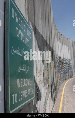 JERUZALEM, ISRAEL - JULI 11, 2004: Welcome to Jerusalem-sign on the Israeli separation or security wall with Palestine covered with activist graffiti. - Stock Photo