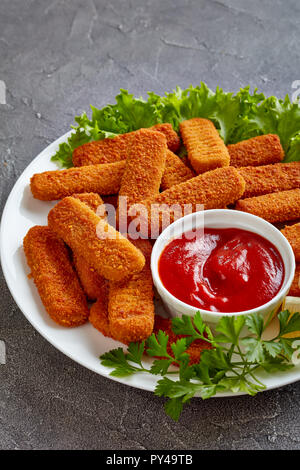 crumbed fish sticks served on a white plate with lemon, lettuce leaves and tomato sauce, vertical view from above - Stock Photo