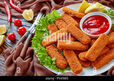crumbed fish sticks served on a white plate with lemon, lettuce leaves and tomato sauce, horizontal view from above, close-up - Stock Photo