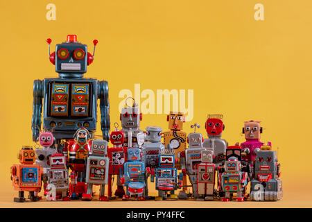 Vintage tin robot toys isolated on a yellow background. - Stock Photo