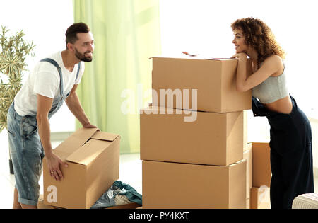 young couple unpacking boxes in a new house - Stock Photo